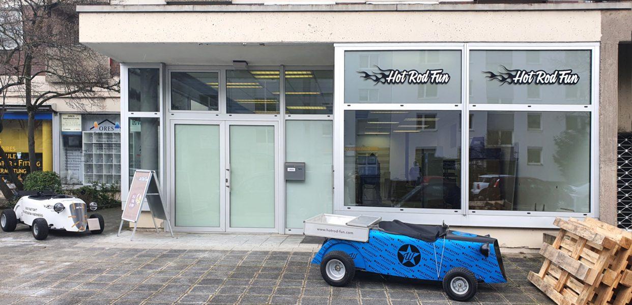 Hot Rod Laden in Nürnberg mit zwei Hot Rod Fahrzeugen davor. Hier sieht man die neue Beklebung der Oberlichter der Schaufenster.