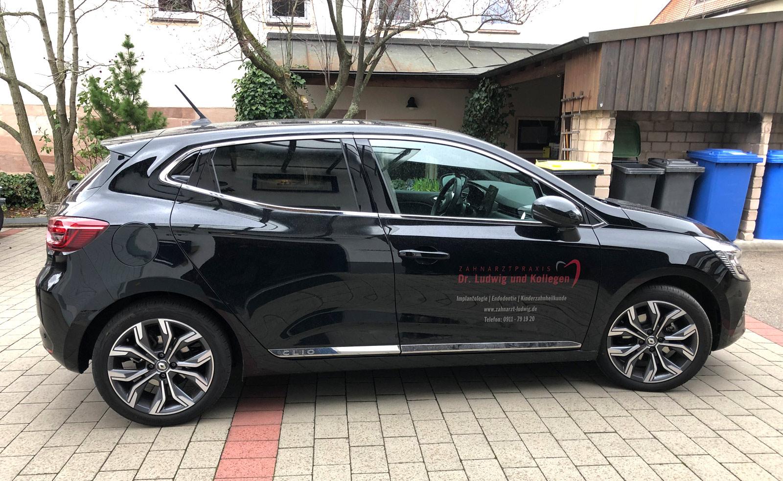 Seitenansicht eines schwarzen Fahrzeugs mit Beklebung für Dr Ludwig und Kollegen