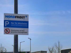 Parkplatzschild der Firma Nordost an einem Laternenpfosten