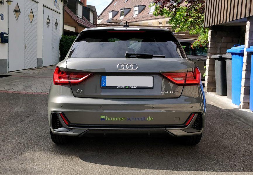 Heckansicht eines dunkelgrauen Audi A1 mit neuer Fahrzeugfolierung mit dem Logo und der Emailadresse