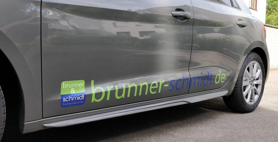 Schräge Seitenansicht eines dunkelgrauen Audi A1 mit neuer Fahrzeugfolierung mit dem Logo und der Emailadresse