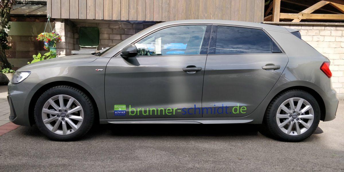 Seitenansicht eines dunkelgrauen Audi A1 mit neuer Fahrzeugfolierung mit dem Logo und der Emailadresse