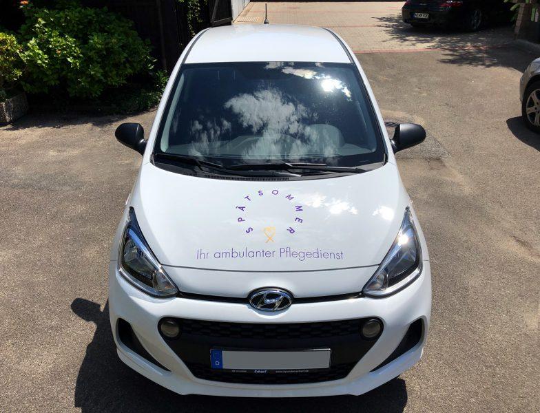 Frontansicht eines weißen Hyundai i10 mit neuer Folienbeschriftung für den Spätsommer Pflegedienst