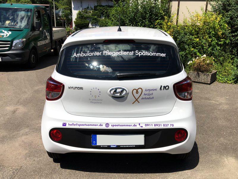 Heckansicht eines weißen Hyundai i10 mit neuer Folienbeschriftung für den Spätsommer Pflegedienst