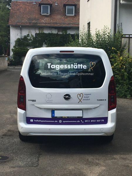 Heckansicht eines weißen Opel Combo mit neuer Beklebung für Spätsommer