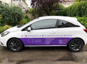 Seitenansicht eines neu folierten weißen Opel Corsa für den Spätsommer Pflegedienst
