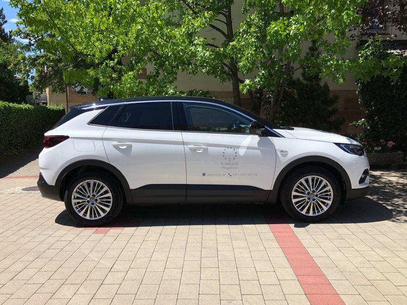 Seitenansicht eines weißen Opel Grandland mit einer neuen dezenten Türbekebung für den Spätsommer Pflegedienst