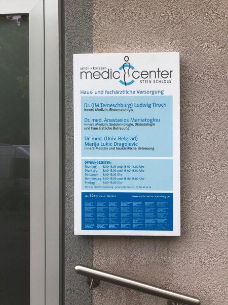 Neu foliertes und montiertes Schild neben dem Eingang an der Wand der Medic Center Praxis in Schloss Stein