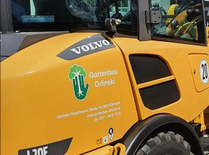 Gelber Radlader aus der Schrägansicht mit neuer Folienbeschriftung für Gartenbau Orlinski