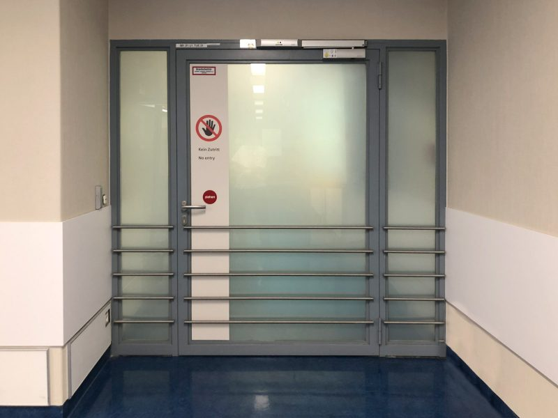 Beklebung einer Wartezimmertüre mit matt laminierter Klebefolie und Verbotszeichen in der Universitätsklinik Erlangen.