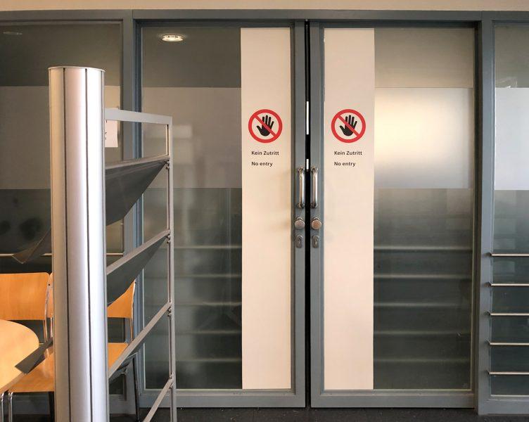 Beklebung einer Doppelschiebetüre mit farbigen Streifen und Hinweisaufklebern in der Universitätsklinik Erlangen.