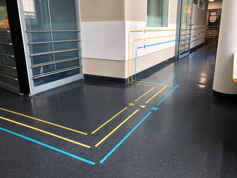 Leitsystem in unterschiedlichen Farben auf dem Fußboden und an der Wand