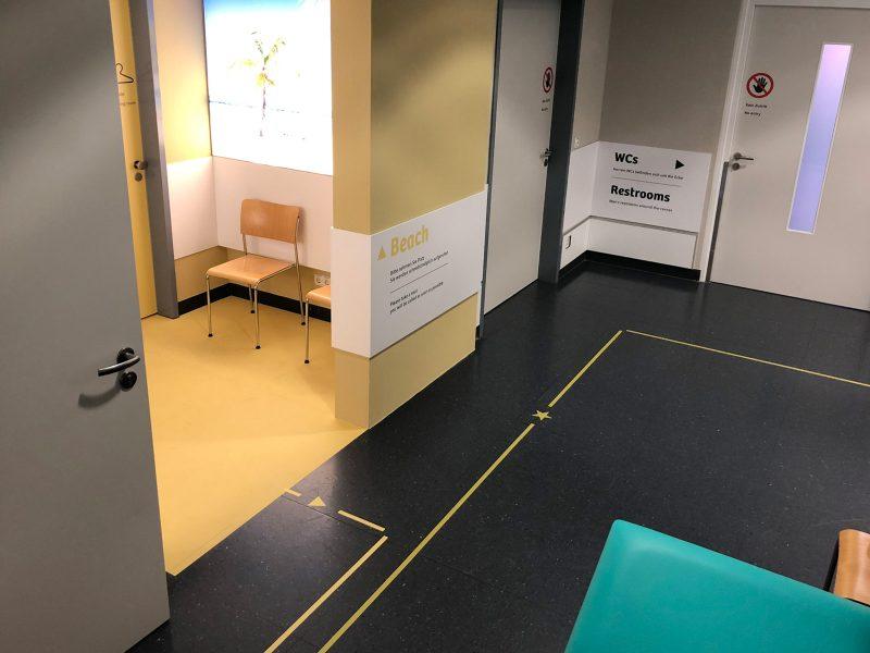 Wartezimmer in der Uniklinik mit Leitsystem und beklebtem Fußboden in gelber Farbe