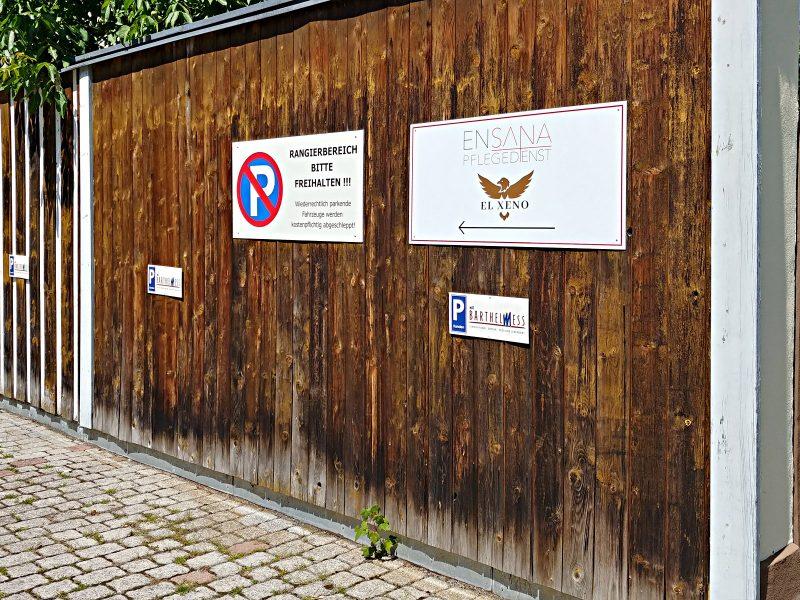 Ein foliertes Firmenschild aus Alu-Dibond an einer Holz-Außenwand dient als Wegweiser für den Ensana Pflegedienst und El Xeno