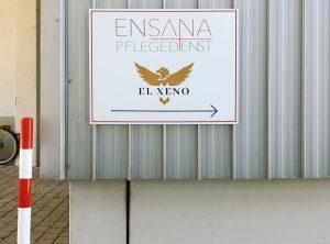 Ein foliertes Firmenschild aus Alu-Dibond an einer Außenwand dient als Wegweiser für den Ensana Pflegedienst und El Xeno
