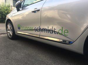 Schräge Seitenansicht eines silbernen Renault Clio mit neuer Folienbeschriftung für Brunner und Schmidt