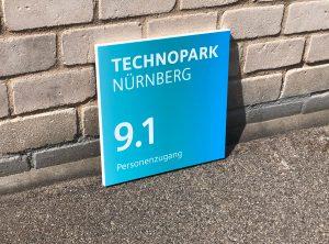 Seitenaufnahme: Ein Schild mit neuer Folienbeschriftung an eine Mauer gelehnt für Siemens Technopark Nürnberg