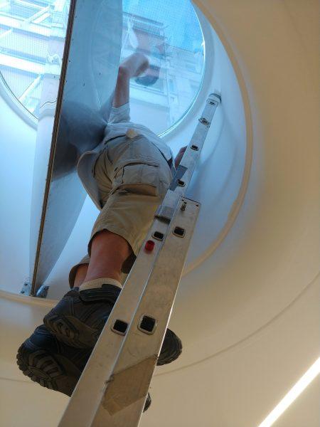 Auf einer Leiter stehender Mitarbeiter von uns der eine Lichtkuppel von innen mit Sonnenschutzfolie beklebt
