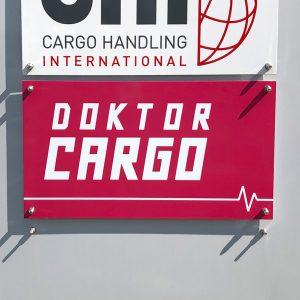 Schild von Doktor Cargo im Detail an eine Stele geschraubt