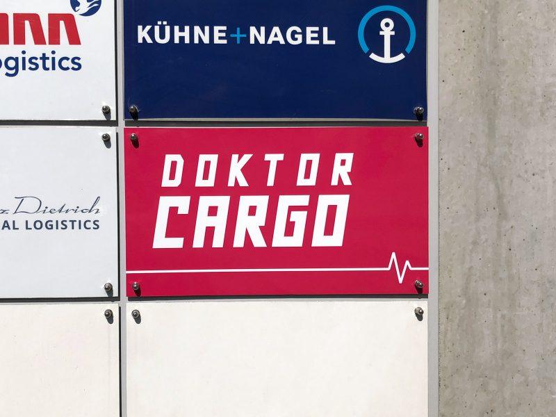 Schild von Doktor Cargo an einer Schildertafel im Detail