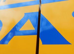 Detailansicht des Aufklebers auf der Seite eines gelben Baggers für Tadas
