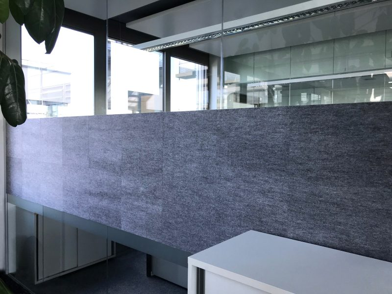 Schallschutzbeklebung aus grauem Stoff an einer Glaswand in einem Büroraum bei IT2media