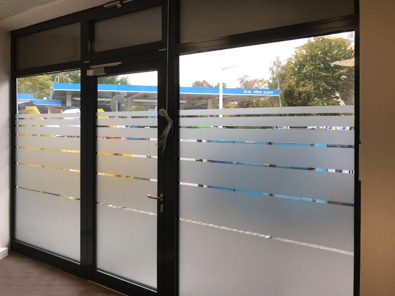 Streifenbeklebung als Sichtschutz von innen fotografiert. Man sieht zwei Fenster und eine Türe mit dem Sichtschutz bei einer Filiale von Hörgeräte Seifert.