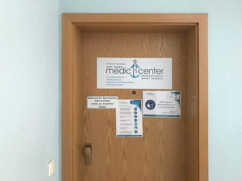 Alu-Dibond Schild, das frisch foliert an der Praxiseingangstüre im Treppenhaus für den Medic Center in Markt Erlbach montiert wurde
