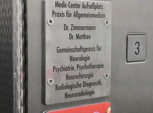 Edelstahlschild graviert und schwarz ausgelegt in einem Aufzug für Medic Center in Nürnberg