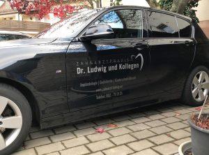 Seitenansicht eines schwarzen BMW 1er mit dezenter Folienbeschriftung für die Zahnarztpraxis Dr. Ludwig aus Fürth