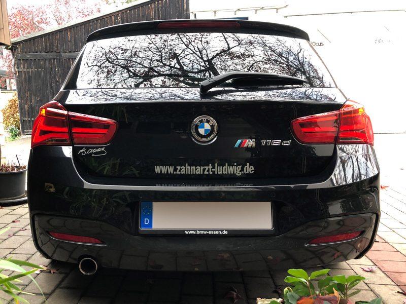Heckansicht eines schwarzen BMW 1er mit dezenter Folienbeschriftung für die Zahnarztpraxis Dr. Ludwig aus Fürth