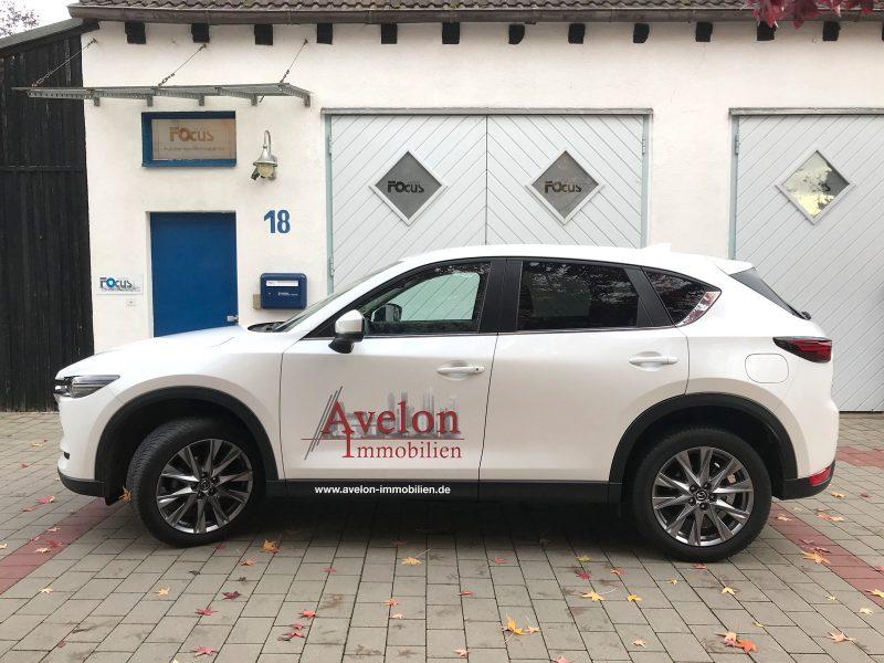 Seitenansicht eines weißen Mazda CX5 mit neuer Folienbeschriftung auf der Fahrerseite für Avelon