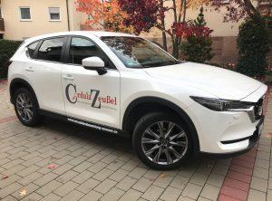 Seitenansicht eines weißen Mazda CX5 mit neuer Folienbeschriftung auf der Beifahrerseite für Cordula Zeußel