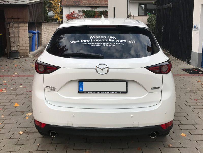 Heckansicht eines weißen Mazda CX5 mit neuer Folienbeschriftung auf der Windschutzscheibe für Immobilienbewertung Zeußel