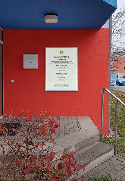 Ein Leuchtschild, das an der rot angestrichenen Hauswand im Eingang der Zahnarztpraxis Baramov hängt