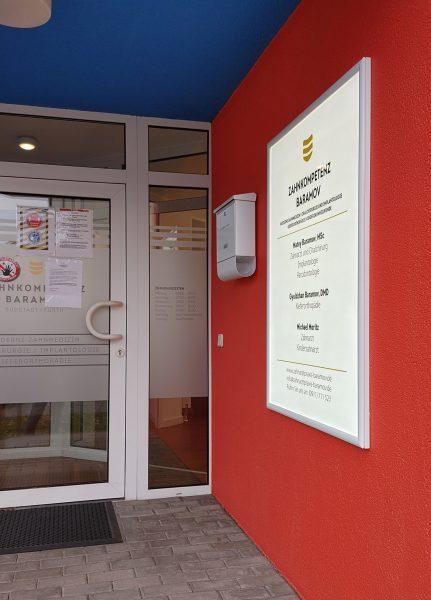 Leuchtschild das von der Seite fotografiert wurde, wie es an der rot angestrichenen Hauswand im Eingang der Zahnarztpraxis Baramov hängt