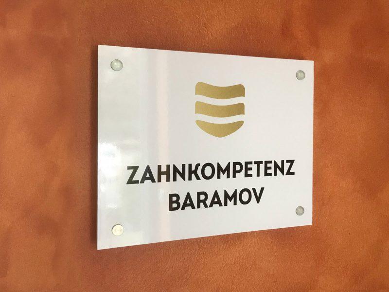 Acrylglasschild an einer roten Wand bei Zahnkompetenz Baramov