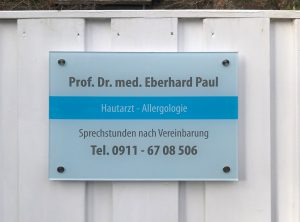 Nahaufnahme: Foliertes Acrylschild am Gartenzaun für den Hautarzt Prof. Dr. med. Eberhard Paul