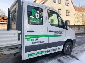 Seitliche Ansicht der Fahrzeugbeklebung eines weißen VW Crafteres für Greenkeepers Gartenbau