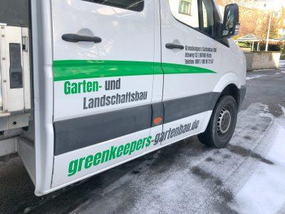 Seitliche Ansicht aus der Nähe: der Fahrzeugbeklebung eines weißen VW Crafteres für Greenkeepers Gartenbau