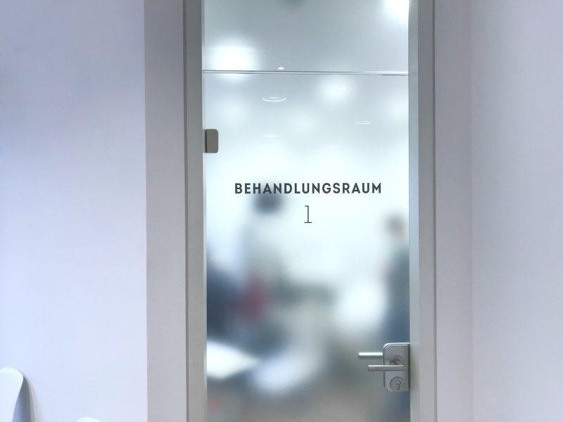 Türbeschriftung in der Zahnarztpraxis Baramov in Fürth. Man sieht die frisch beklebte Glastüre eines Behandlungsraumes