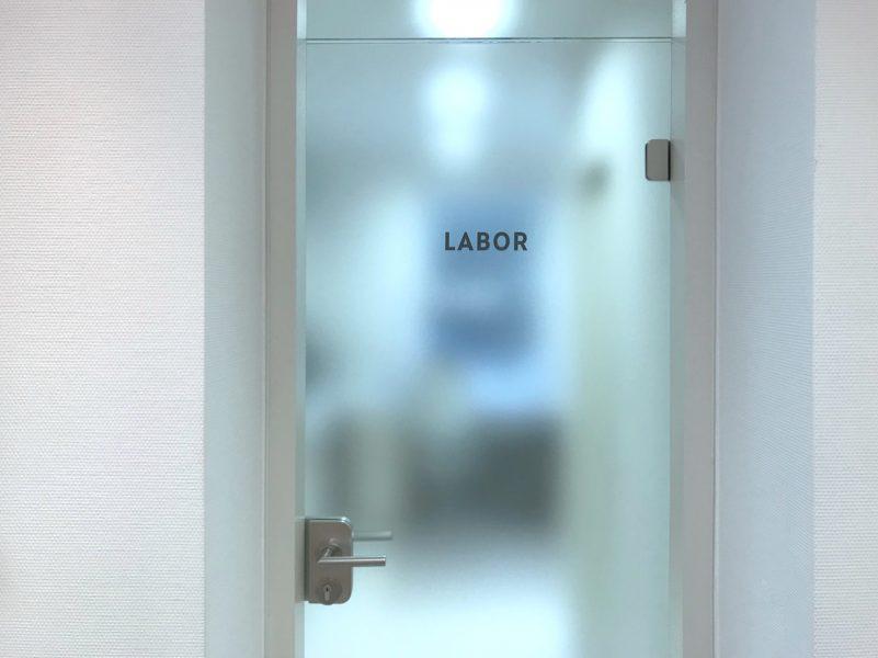Türbeschriftung in der Zahnarztpraxis Baramov in Fürth. Man sieht die frisch beklebte Glastüre eines Labors