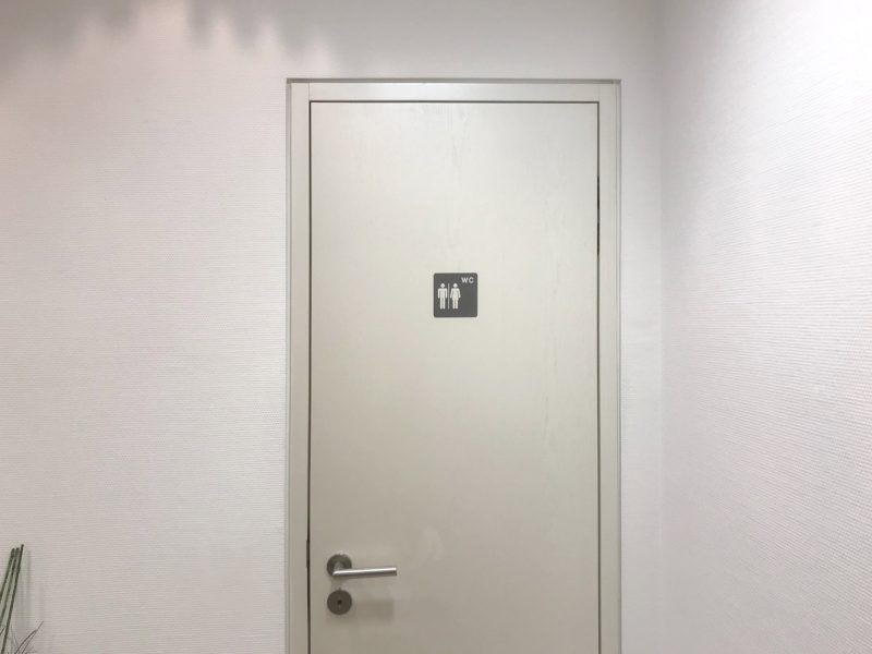 Türbeschriftung in der Zahnarztpraxis Baramov in Fürth. Man sieht die frisch beklebte Toilettentüre