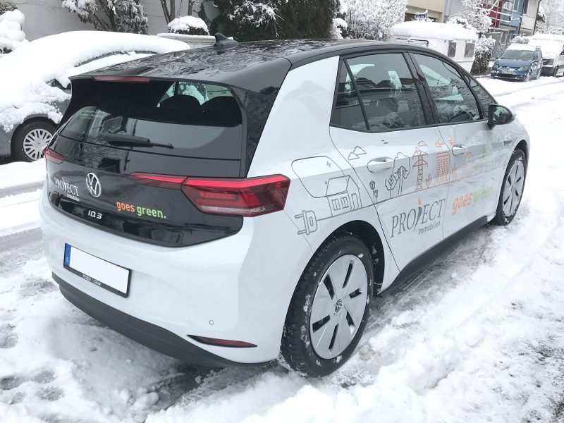 Schräg von rechts hinten fotografierte Fahrzeugbeklebung eines VW ID 3 für Project Immobilien
