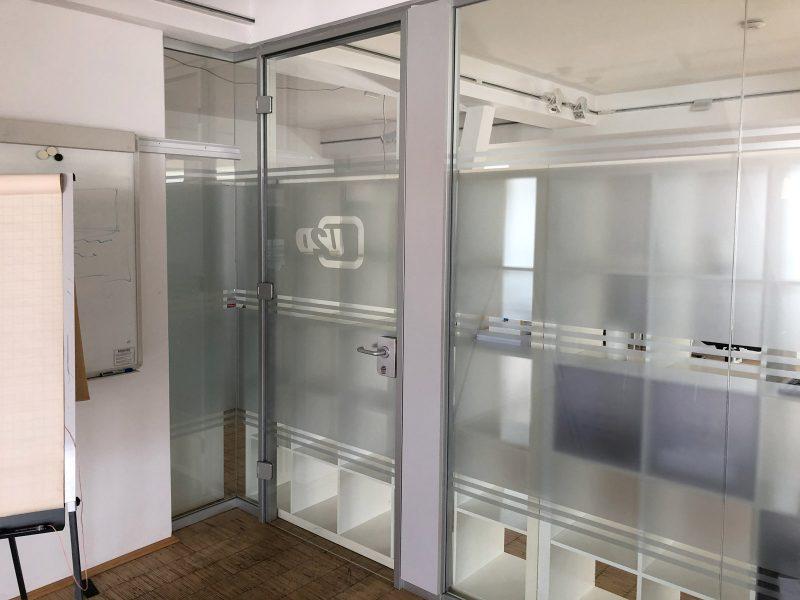 Sichtschutzfolierung aus Milchglasfolie an einer Büroglaswand und Türe bei up2date