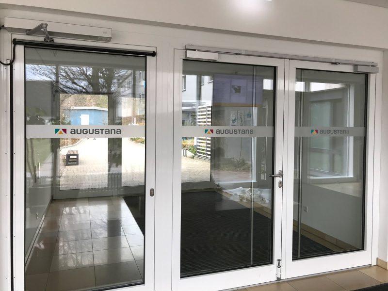Durchlaufschutz mit Logo an drei Glaseingangstüren
