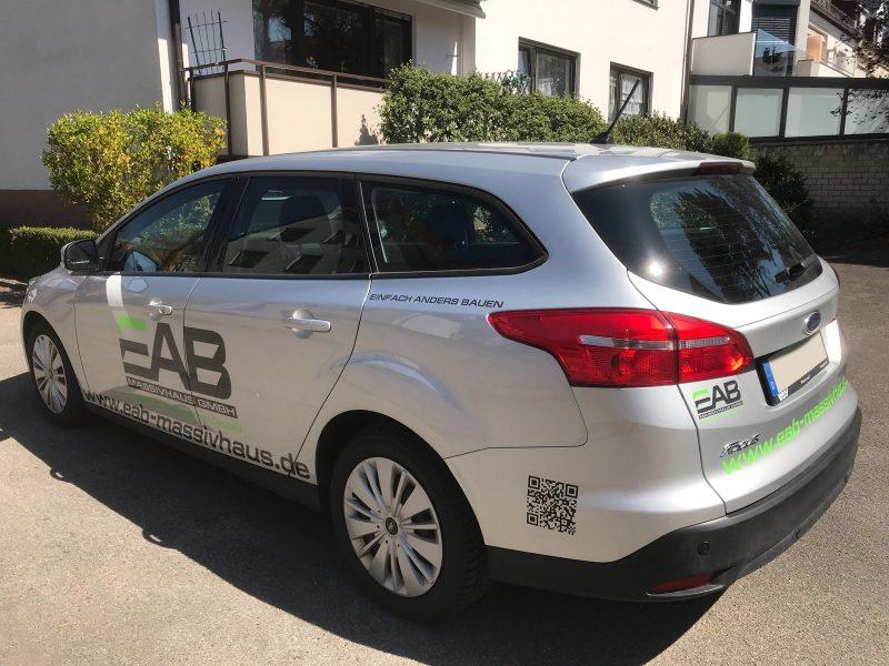 Fahrzeugfolierung - Heck- und Seitenansicht eines Ford Focus für EAB Massivhaus