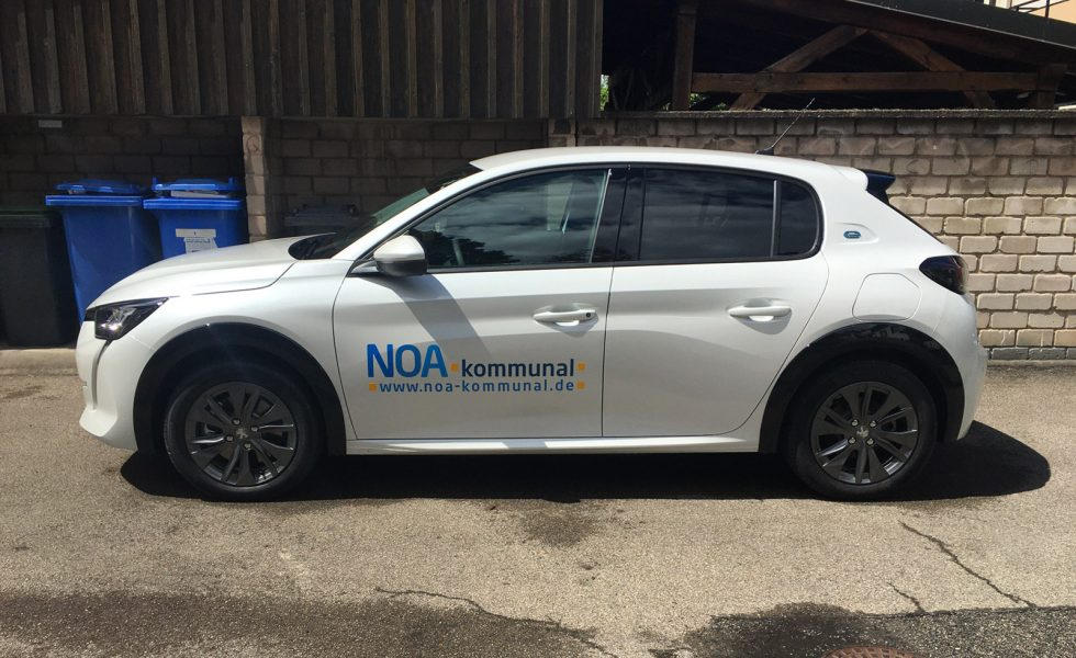 Fahrzeugbeschriftung - Seitenansicht des weißen Peugeot e-208 für NOA kommunal