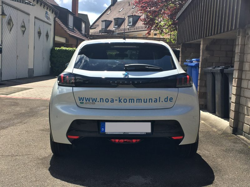 Fahrzeugbeschriftung - Heckansicht des weißen Peugeot e-208 für NOA kommunal