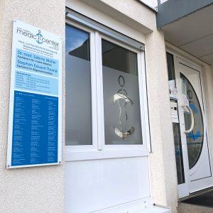 Praxis-Beklebungen - Sichtschutzfolierung und Alu-Dibond Schild am Eingang eines Medic Centers